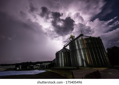A tornado-warned thunderstorm approaches grain silos in Iowa, illuminated by lightning at night.