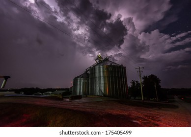 A tornado-warned thunderstorm in Iowa illuminated by lightning approaches a grain silo.