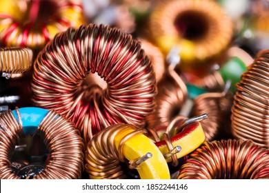 Toroidale elektronische Induktoren auf Halde auf elektrotechnischem Hintergrund. Nahaufnahme von schönen Induktionsspulen mit Kupferdraht, der auf Magnetkernen aufrollt. Farbige Bauteile der Elektrotechnik.