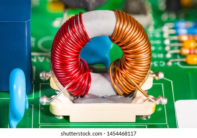 Toroidal transformer coil. Colorful wire winding on inductor with ferrite core. Electronic components on green circuit board from disassembled power supply. Inverter close-up. Electrical engineering.