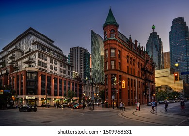 Toronto, ON—Sept 17, 2019; pedestrians and cars moving across roads and sidewalks around the corner of flat iron building in downtown at sunset