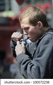 TORONTO - APRIL 20:  A young man lighting his metal marijuana  pipe during the annual marijuana 420 event at Yonge & Dundas Square  on April 20  2012 in Toronto, Canada.