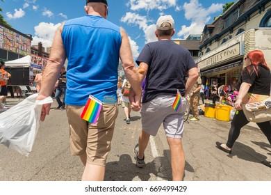 Toronto, CA - 24 June 2017: Gay couple holding hands and walking on Church Street in the Gay Village.