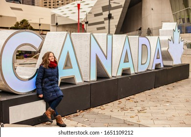 Toronto, Canada- 11.22.2018 : Teen girl posing in downtown Toronto. Stella with the inscription canada is a favorite place for tourists to take pictures.
