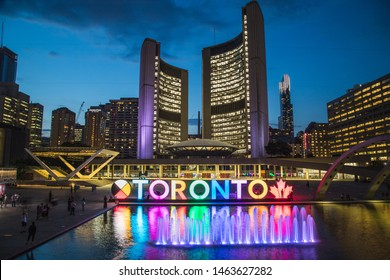 TORONTO, CANADA - 17TH JULY 2019: The Toronto Sign at Nathan Phillips Square with the City Hall and other architecture in the background. Taken at night. People can be seen.