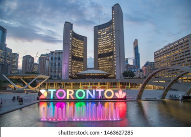 TORONTO, CANADA - 17TH JULY 2019: The Toronto Sign at Nathan Phillips Square with the City Hall and other architecture in the background. People can be seen.