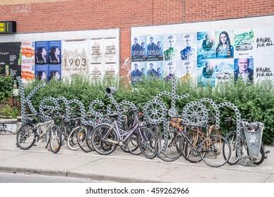Toronto, Canada - 2 July 2016: Bike racks and Kensington neighbourhood metal sign in Toronto, Canada.