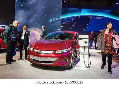 Toronto, Canada - 2018-02-19 : Visitors of 2018 Canadian International AutoShow beside the new 2018 Chevrolet Volt electric car on the Chevrolet division of General Motors Corporation exposition