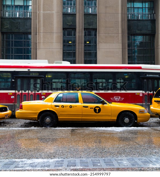 TORONTO, CANADA - 22ND FEBRUARY 2015: A New York City Taxi in downtown Toronto during the day. A Streetcar can be seen behind it
