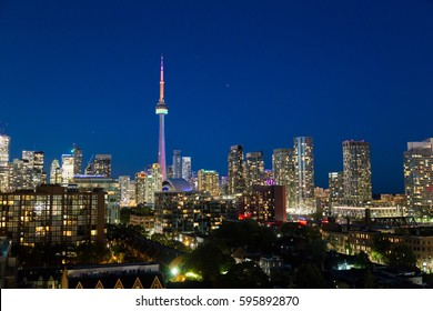 TORONTO, CANADA - 23RD JUNE 2015: The Toronto Skyline at night showing buildings and architecture. The CN Tower can be seen showing the colors of World Pride