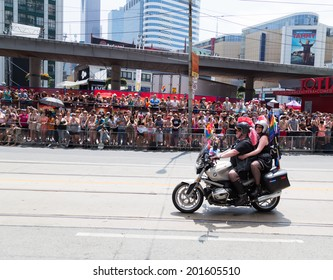 TORONTO, CANADA - 29TH JUNE 2014: People participating in the World Pride Parade in Toronto. Spectators can be seen beside the path.