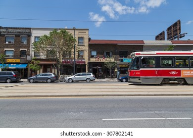 TORONTO, CANADA - 2ND JUNE 2015: Buildings along St Clair West in Toronto during the day. A Streetcar can be seen and other vehicles.