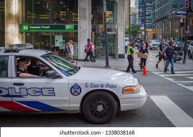 TORONTO, CANADA - APRIL 17, 2018:  Toronto Police in a police car on duty in front of TD Canada Trust bank in Downtown Toronto