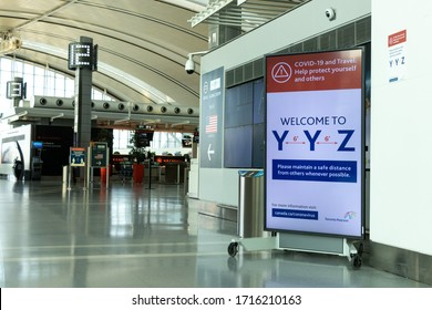 TORONTO, CANADA - April 18, 2020: Social distancing warning sign posted inside a vacant Terminal 1 at Toronto Pearson Intl. Airport during the peak of the COVID-19 pandemic.
