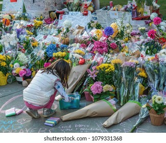 TORONTO, CANADA - APRIL 27, 2018:  A girl is writing blessings with a chalk , at Mel Lastman Square, at a memorial for the victims of of van rampage on Young Street in North  York