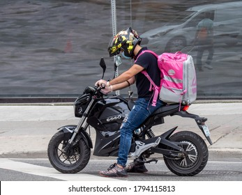 Toronto  Canada, August 11, 2020; a restaurant food courier on a motorcycle with a Foodora backpack on Queen Street in Toronto.