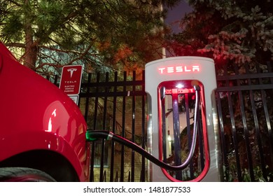 TORONTO, CANADA - August 15, 2019: Tesla Supercharger seen at night with Red Tesla vehicle plugged-in, charging.