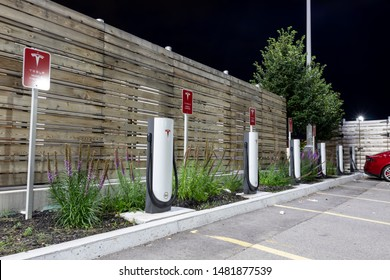 TORONTO, CANADA - August 15, 2019: Tesla Supercharger Station seen on a clear night with vehicle plugged-in.