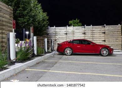 TORONTO, CANADA - August 15, 2019: Red Tesla Model S charging at Tesla Supercharger under bright lights at night.