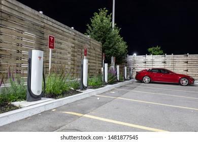 TORONTO, CANADA - August 15, 2019: Tesla Model S supercharging at night.