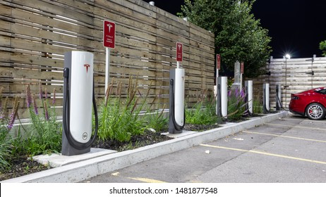 TORONTO, CANADA - August 15, 2019: Tesla Supercharger Station seen on a clear night with Red Tesla Model S charging in the background.