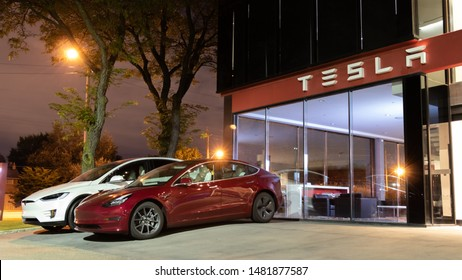 TORONTO, CANADA - August 15, 2019: Red Tesla Model 3 and White Tesla Model X parked out-front of a Tesla Showroom at night.