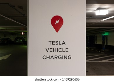 TORONTO, CANADA - August 20, 2019: Tesla Supercharger logo and Tesla Vehicle Charging text on post in parking garage in-front of Tesla Supercharger Station.