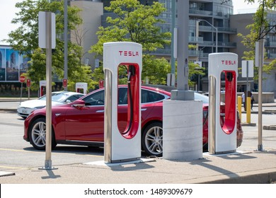 TORONTO, CANADA - August 20, 2019: Tesla Supercharger Station seen with red Tesla Model S and white Tesla Model S in the background at sunny day.