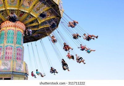 TORONTO, CANADA - AUGUST 25, 2014: Swing ride at Canadian National Exhibition in Toronto, Ontario, Canada. CNE is largest annual fair in Canada and the seventh largest in North America.