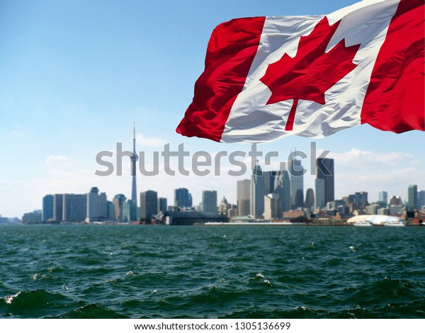 TORONTO, CANADA - Canadian flag is waving front of Toronto City view