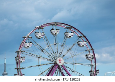 Toronto Canada, Circa August 2019; A Ferris wheel ride at the Canadian National Exhibition CNE in Toronto with the CN Tower in the background