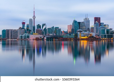 TORONTO, CANADA - CIRCA NOVEMBER 2017: Toronto city skyline as seen across Lake Ontario from Polson Pier around sunrise. CN tower and the downtown cityscape reflected in the water.