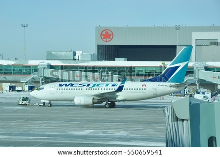 Toronto, Canada - December 17, 2016: Westjet plane seen park at the snowy tarmac of Toronto Pearson International Airport.