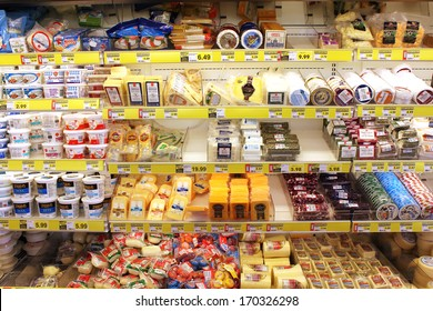 TORONTO, CANADA - DECEMBER 18, 2013: Variety of cheeses on shelves in a grocery store. Hundreds of types of cheese are produced by various countries with different styles, textures and flavors.