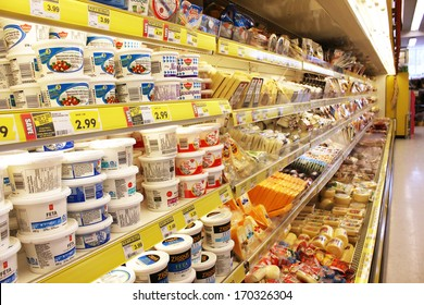 TORONTO, CANADA - DECEMBER 18, 2013: Different brands of cheese on shelves in a grocery store. Hundreds of types of cheese are produced by various countries with different styles, textures and flavors