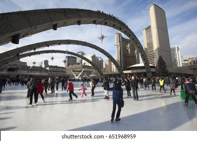 TORONTO, CANADA. December 26, 2014: Toronto City Hall or New City Hall, people skating in the rink in Toronto, Canada. The City Hall is the home of the municipal government of the city.
