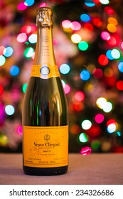 """TORONTO, CANADA - DECEMBER 29, 2013: A bottle of """"Veuve Clicquot"""" fine champagne with blurred Christmas lights on a background. An illustration for winter holidays spirit."""