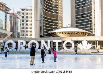 TORONTO, CANADA - JANUARY 23, 2021: PEOPLE SKAKE AT ICE RINK AT NATHAN PHILLIP SQUARE WITH 'TORONTO' SIGN BEHIND THEM DURING COVID-19 PANDEMIC.