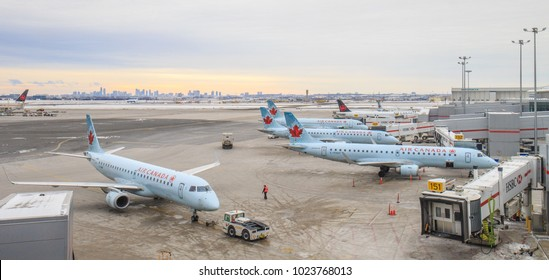 TORONTO, CANADA - JANUARY 8, 2018: Air Canada Embraer 190 passenger jets arrive at the terminal building of Toronto Pearson International Airport at dawn. The Toronto skyline is visible.
