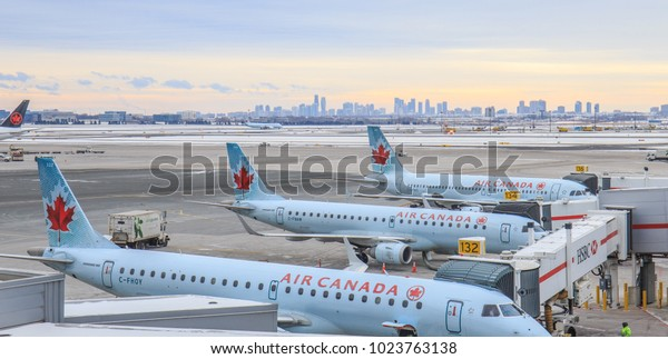 TORONTO, CANADA - JANUARY 8, 2018: Air Canada Embraer 190 regional passenger jets arrive at the terminal building of Toronto Pearson International Airport at dawn. The Toronto skyline is visible.