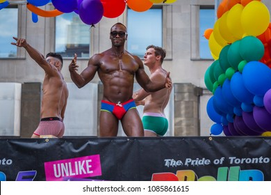 TORONTO, CANADA -  JULY 03, 2016: Toronto Pride 2016 . Afro American male  in colorful underwear is dancing with other two men in underwear on a decorated truck with balloons and slogans