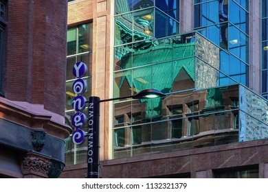 TORONTO, CANADA - JULY 11, 2018:   A sign on a street light, between modern and an ancient buildings facades at Yonge Street in Toronto, showing the location