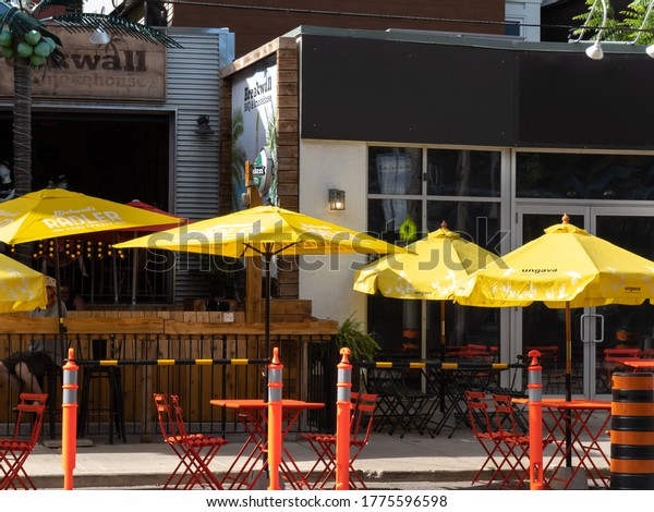 Toronto Canada, July 13, 2020; Umbrellas on street curb lane patios in Toronto to allow restaurants to serve customers during the covid-19 pandemic phase 2 reopening