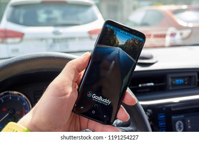 TORONTO, CANADA - JULY 15, 2018: GasBuddy mobile app on s8 screen in a hand. GasBuddy is company that operates apps and websites based on finding real-time fuel prices