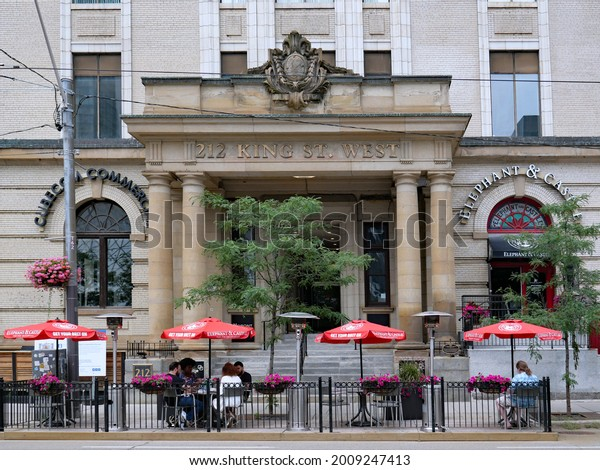 Toronto, Canada - July 16, 2021:  Part of the road is taken over by restaurants on a main street in  Toronto, as outdoor dining is safer during the pandemic.