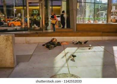TORONTO, CANADA - JULY 21, 2018:  Homeless man is laying down on a concrete floor ,besides a pizza box, in the Financial District of Downtown Toronto