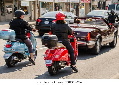 Toronto, Canada - July 22, 2014: Two women on motorcycles chatting in Toronto, Canada