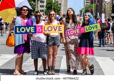 """TORONTO, CANADA - JULY 3, 2016: Five women holding """"LOVE IS LOVE"""" sign at Toronto Pride Parade."""