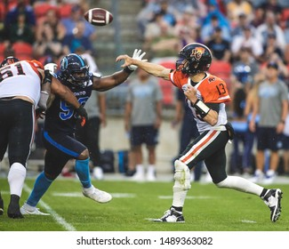 Toronto, Canada - July 6, 2019: BC Lions Quarterback Mike Reilly (13) Throwing down field during BC Lions at Toronto Argonauts game at BMO Field in Toronto, ON