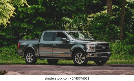 Toronto Canada, July 7 2019: Ford F150 Truck positioned on gravel road in front of lush green foliage